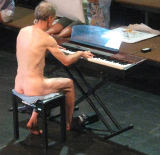 nude man playing piano